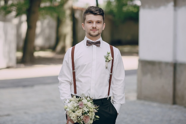 Groom in suspenders with a bouquet