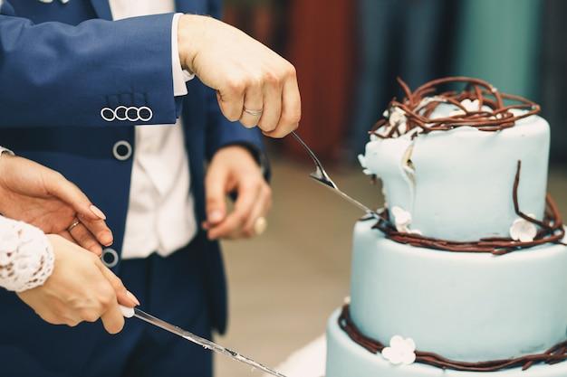 Groom takes piece of blue wedding cake