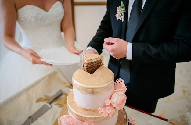 Groom takes a piece of wedding cake covered with golden glaze and decorated with roses
