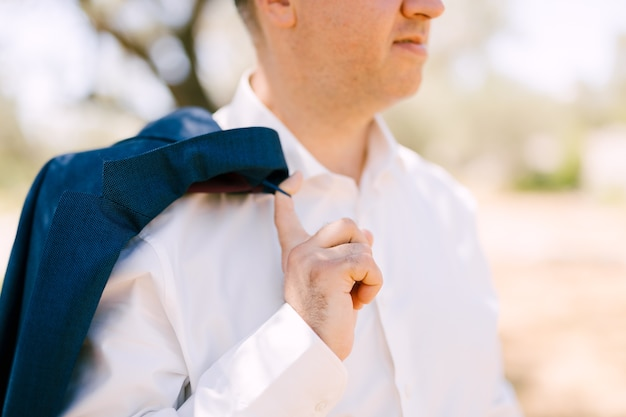 Groom threw the jacket over his shoulder.