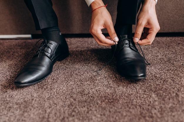 新郎はソファに座って彼の靴のひもを結ぶ