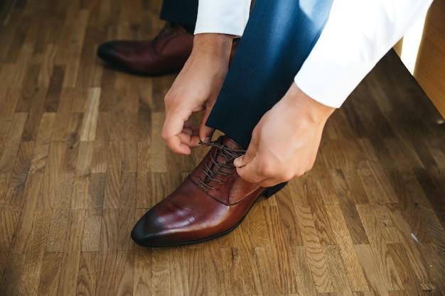 Жених завязывает шнурки на ботинки