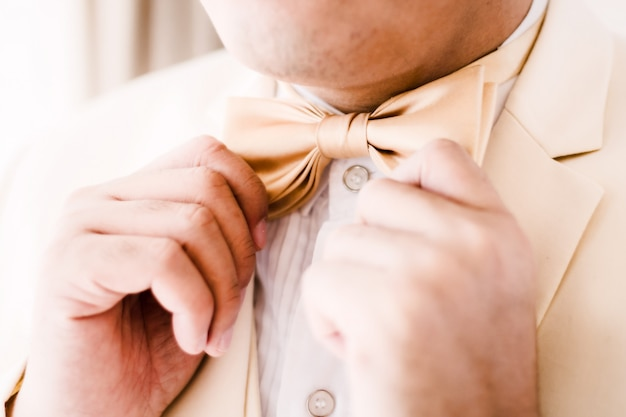 Groom touching bowtie
