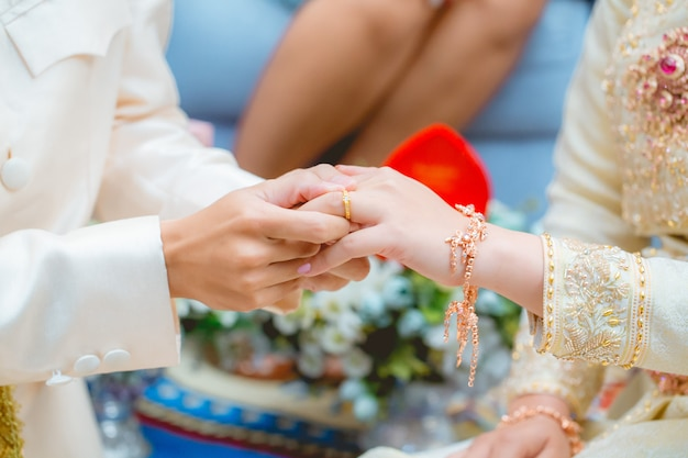 The groom wearing the wedding ring to the bride's finger