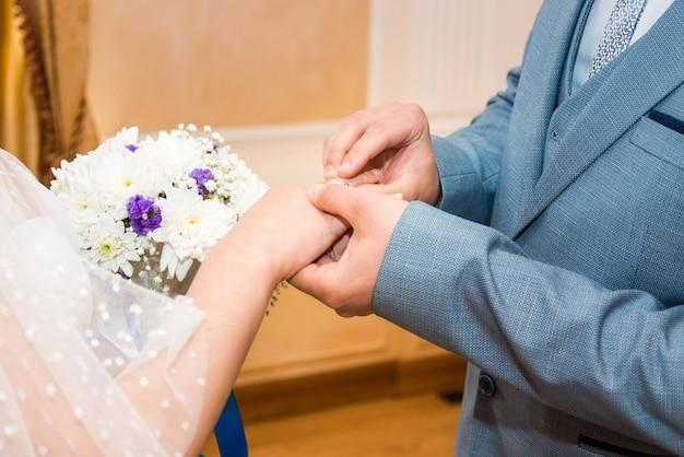 新郎は花嫁に結婚指輪をつけます花嫁の手は美しいウェディングブーケを持っています...