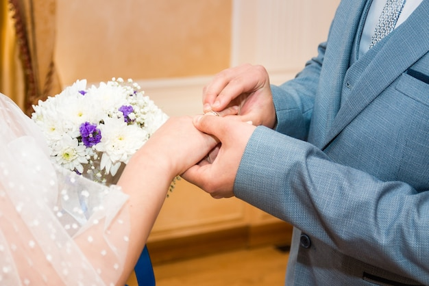 Groom wears bride a wedding ring bride hand holds a beautiful wedding bouquet...