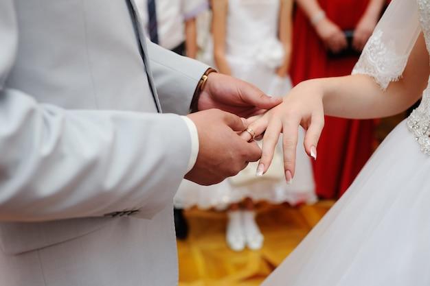 Groom wears a wedding ring a bride
