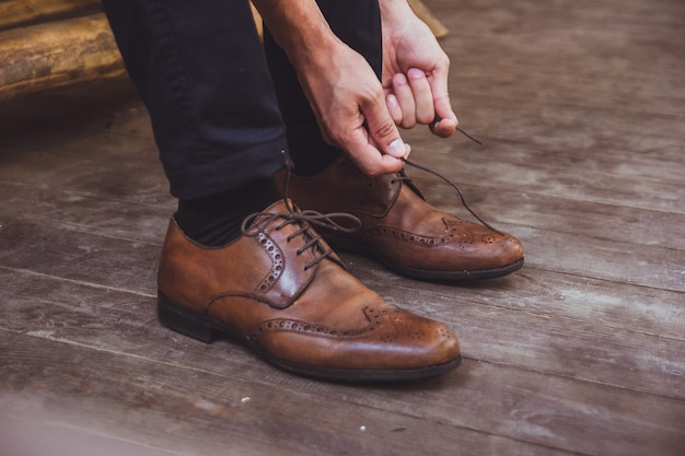 A groom and wedding shoes. groom is wearing shoes outdoors. male portrait of handsome guy.