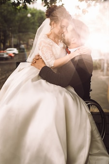 Groom on wheelchair holds bride on his knees sitting outside in the park
