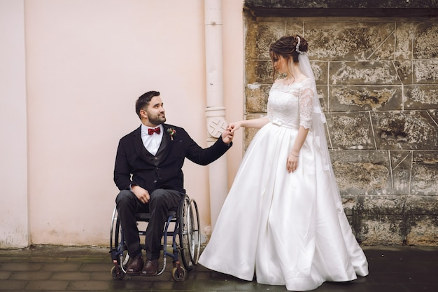 Groom on the wheelchair holds bride's hand standing before old house on the street