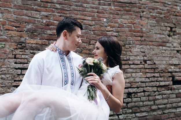 Groom whirls bride on his arms standing before a brick wall