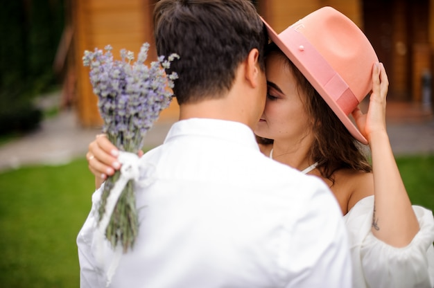 Groom in white shirt hugging bride in white dress and pink hat with bouquet of flowers