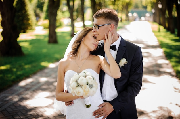 Groom with glasses and bride with a bouquet of peonies gently hug in the park
