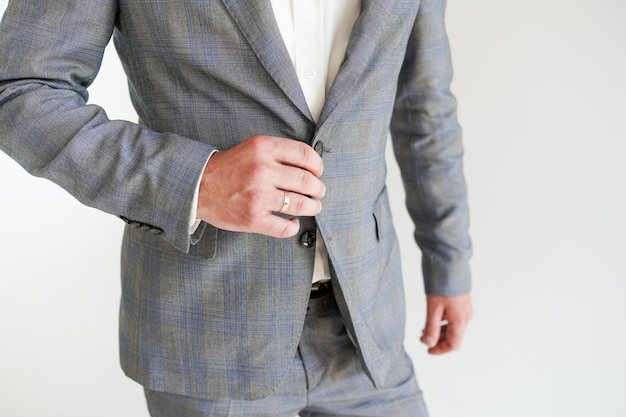 The groom with wedding ring in a grey suit on white