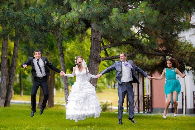 日当たりの良い緑豊かな公園でジャンプ新婦付け添人と花groom付け添人の新婚カップルの完全な長さの肖像画