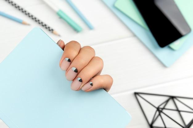 노트 패드를 들고 창조적 인 네일 디자인으로 단정 한 여자의 손