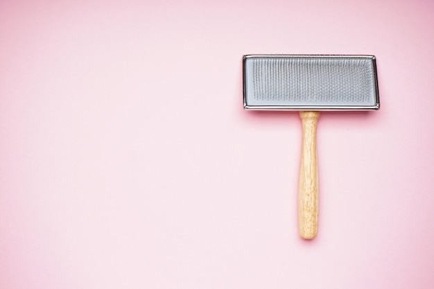 Grooming brush. brush for dogs on a pink background, space for text. flat lay.