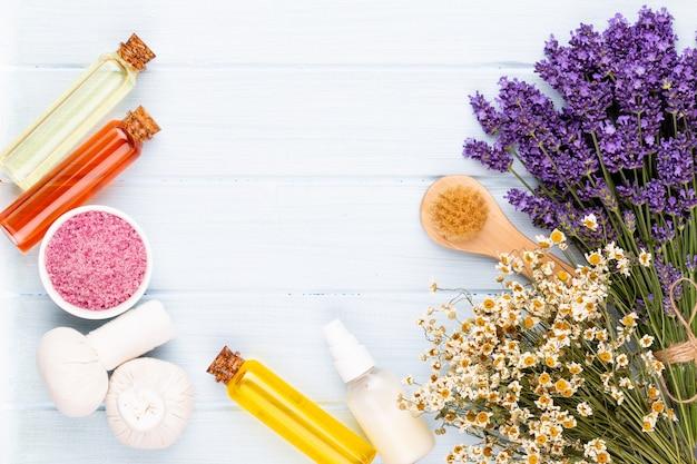 손질 제품 및 흰색 나무 테이블 배경에 신선한 라벤더 꽃다발.
