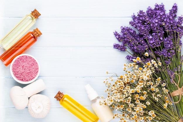 白い木製のテーブルの背景にグルーミング製品と新鮮なラベンダーの花束