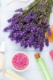 흰색 나무 테이블 배경에 손질 제품과 신선한 라벤더 꽃다발.