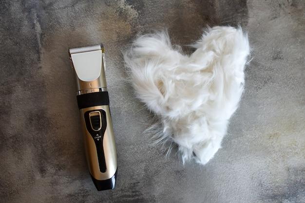 グルーミングツール。灰色の背景に、ハートの形をしたバリカンと動物の毛皮。ペットの世話と愛。