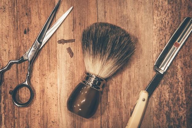 グルーミングツール。木目の上に横たわっている理髪店のツールの上面図