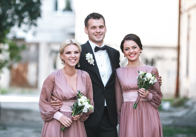 Groomsman embracing two bridesmaids standing outside