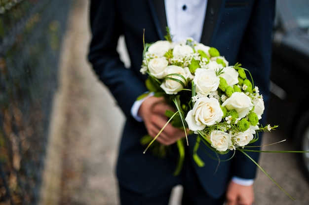 Groomsman hold in hand two bouquets for bridesmaids