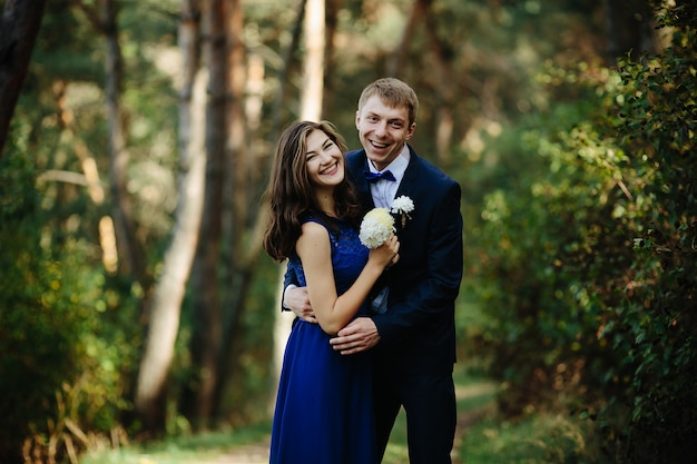 Groomsman hugging bridesmaid standing in forest