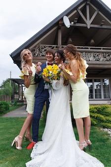 Женихи и подружки невесты с молодоженами на свадебной церемонии