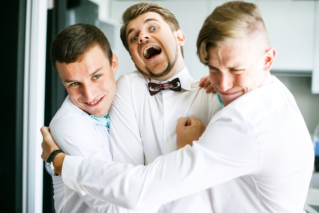 Groomsmen hug tightly bearded groom standing on the kitchen