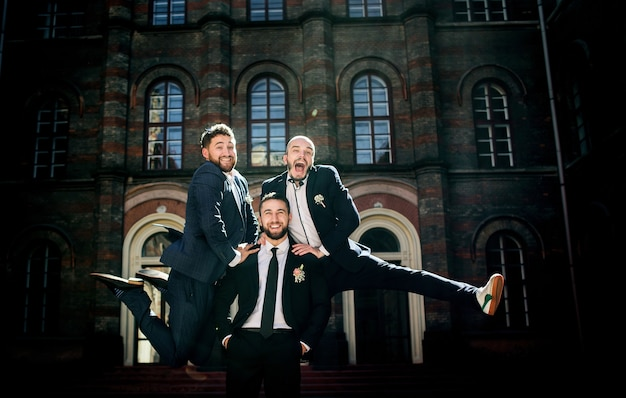 Groomsmen in stylish suits jump on groom's back