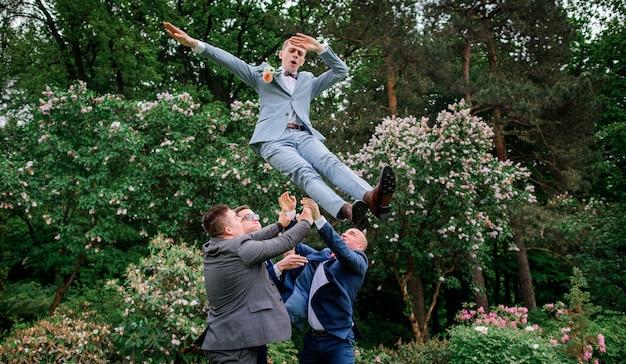 Groomsmen throw groom up standing in the park