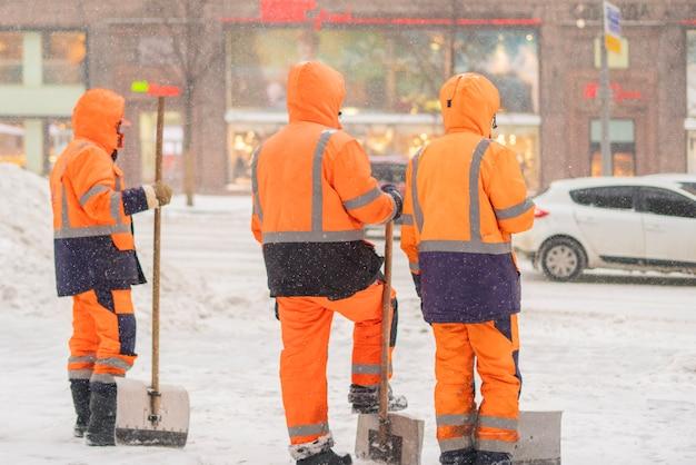 Groop of city janitors stand in snowy street