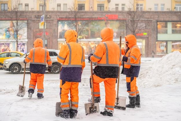 Группа городских дворников стоит на заснеженной улице