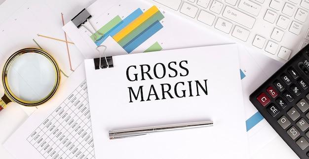Текст gross margin на белой бумаге на светлом фоне с бумагой диаграмм, клавиатурой и калькулятором
