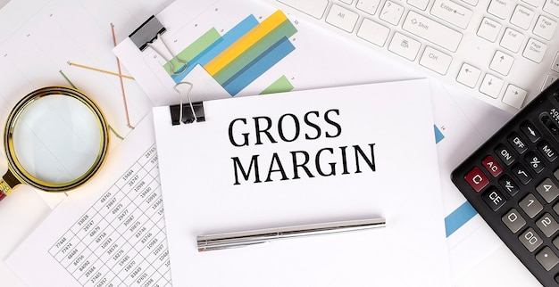Gross margin text on the white paper on the light background with charts paper ,keyboard and calculator