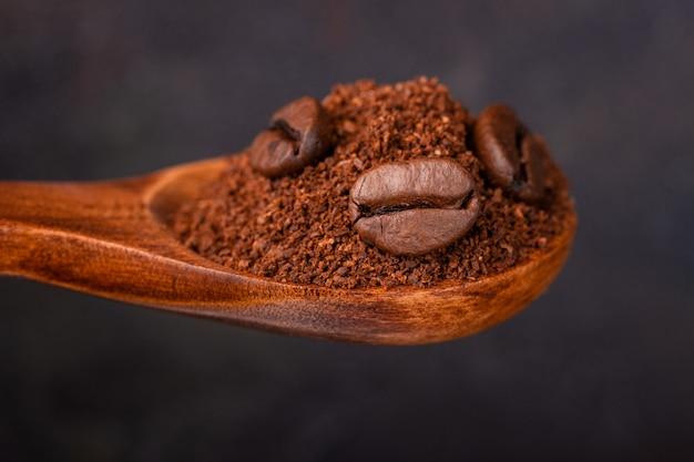 暗い背景に対して木のスプーンで挽いたコーヒーと穀物コーヒー