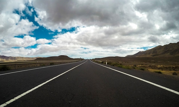 Ground beautiful view of long way straight asphalt road and blue clouds sky