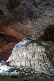 Sotto terra. splendida vista di stalattiti e stalagmiti in una caverna sotterranea - new athos cave. formazioni sacre antiche del mondo sotterraneo.