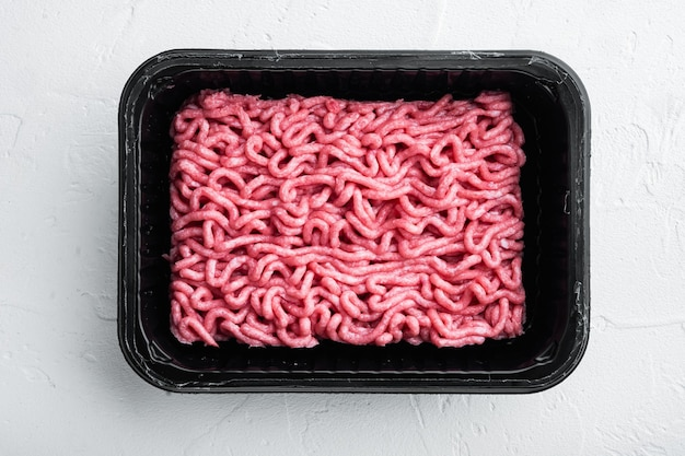 Ground beef meat in plastic tray, on white stone