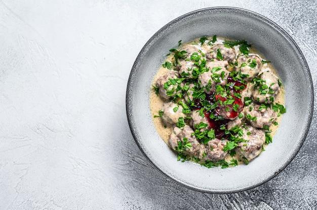 牛ひき肉のミートボールをクリームソースで皿に盛り付けます。白い木製のテーブル。上面図。