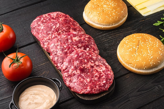 Ground beef patties for grilling and roasting set, on black wooden table background