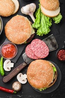 地面の牛肉ステーキ、黒の背景に2つのハンバーガー、フラットレイアウト