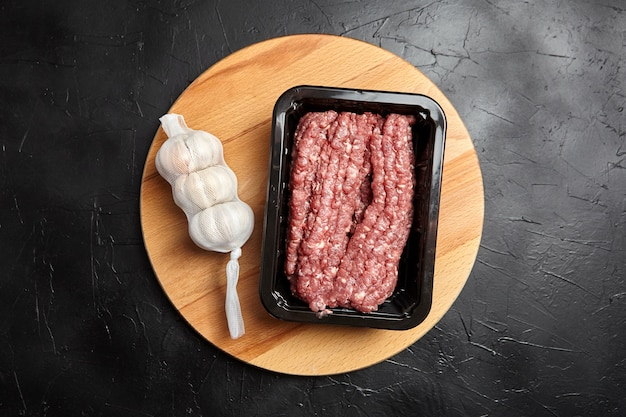 Ground beef in a tray and garlic heads in mesh bag on wooden cutting board on black table, top view