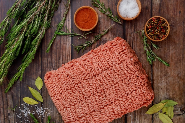 Ground beef with spices and rosemary on wooden table.