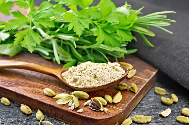 Ground cardamom in a spoon, seasoning capsules, napkin, fresh parsley and rosemary on black wooden board background