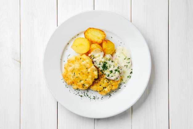 Котлета из куриного фарша с обжаренными картофельными дольками и сливочным соусом с беконом на белом деревянном столе