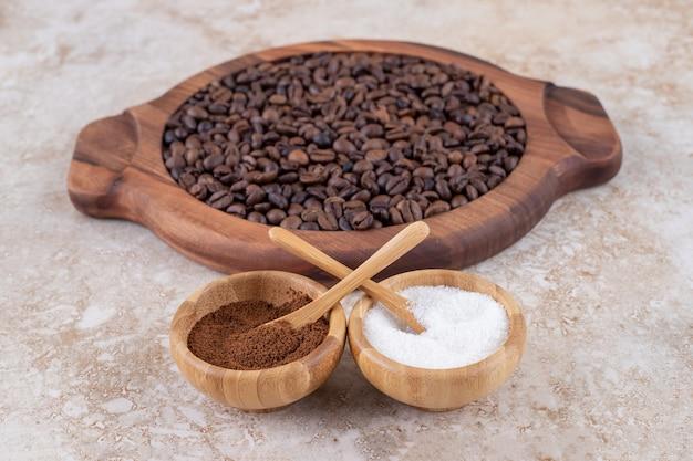 木製のトレイに積み上げられたコーヒー豆の横にある挽いたコーヒーと砂糖入れ