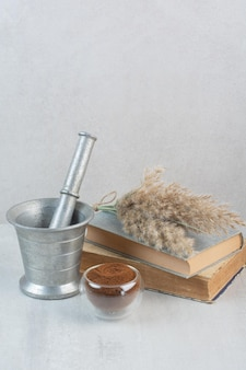 원두 커피, 책, 박격포 및 유봉은 회색 테이블에 있습니다. 고품질 사진